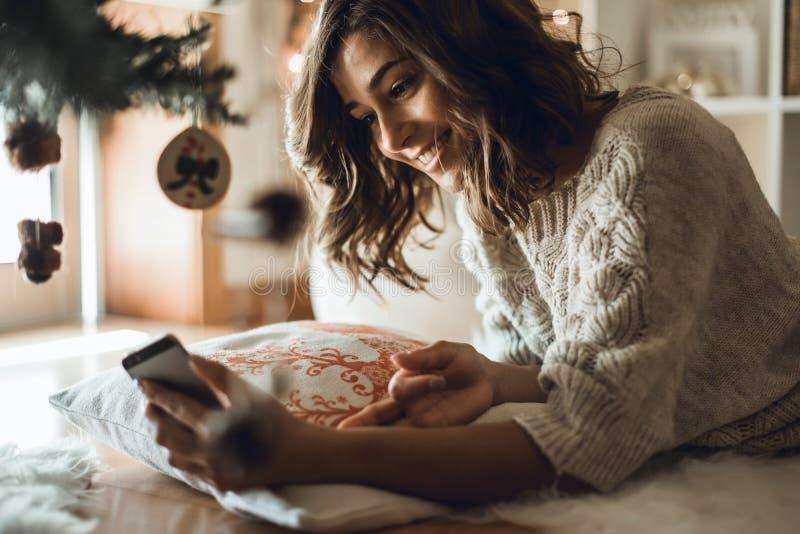 Kvinna som hemma använder en smartphone arkivfoton