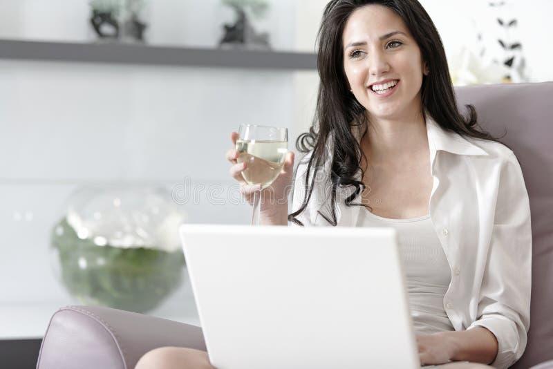 Kvinna som hemma använder hennes bärbar dator fotografering för bildbyråer
