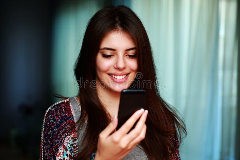 Kvinna som hemma använder smartphonen fotografering för bildbyråer