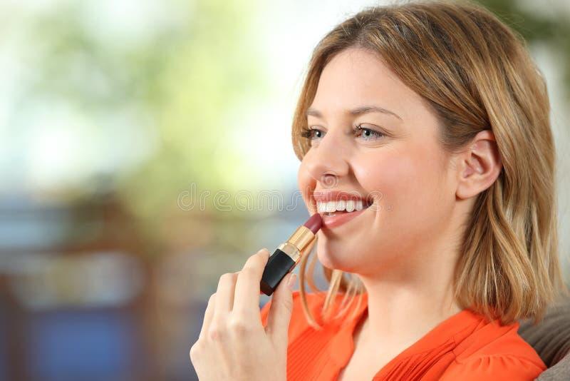 Kvinna som hemma applicerar kanter för en läppstiftmålning royaltyfri foto