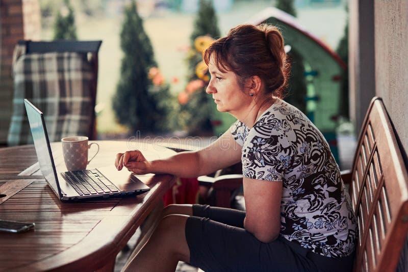 Kvinna som hemma arbetar, genom att använda den bärbara datoren arkivfoton