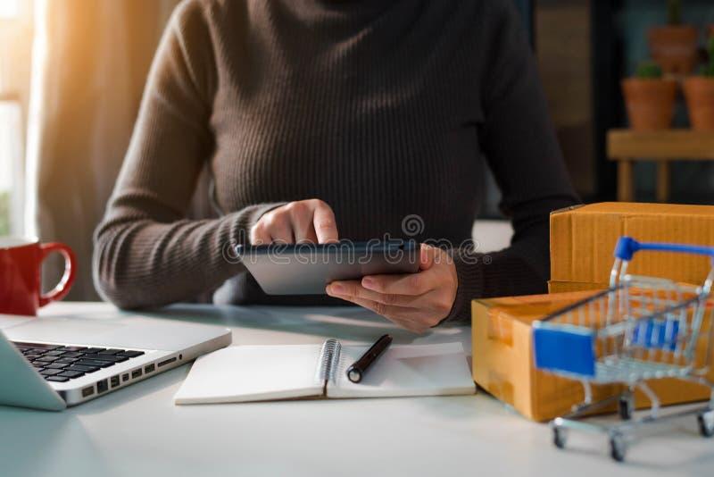 Kvinna som hemma arbetar om online-affär arkivbilder
