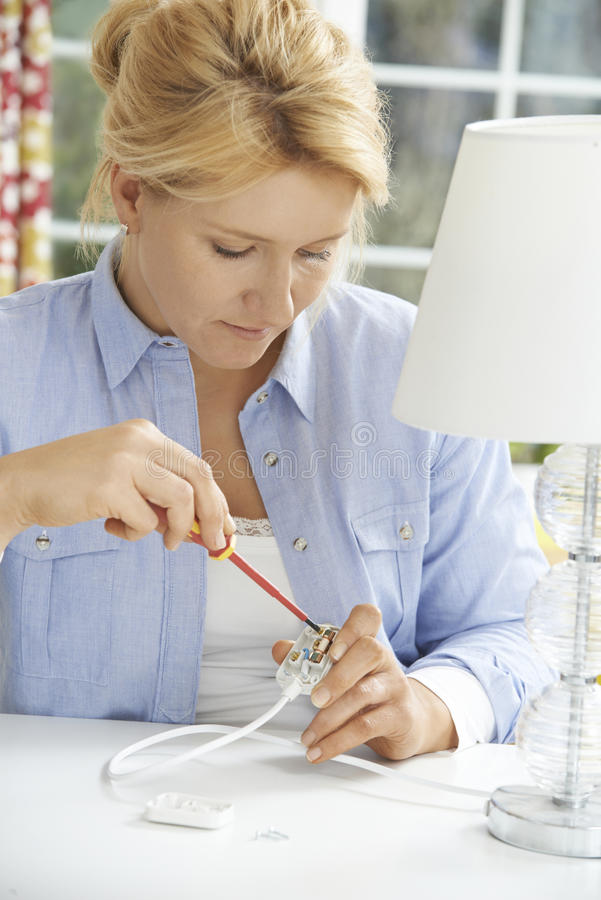 Kvinna som hemma binder den elektriska proppen på lampan arkivfoto