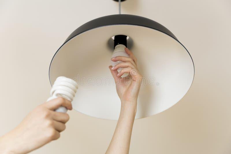 Kvinna som hemma byter ut den ljusa kulan Makt - räddningen LEDDE att ändra för lampa arkivfoton