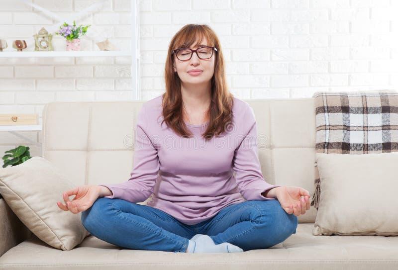 Kvinna som hemma gör yoga i sovrummet Mellersta ålderkvinnlig som inomhus mediterar göra kvinnayoga livsstil- och klimakteriumbeg royaltyfri fotografi