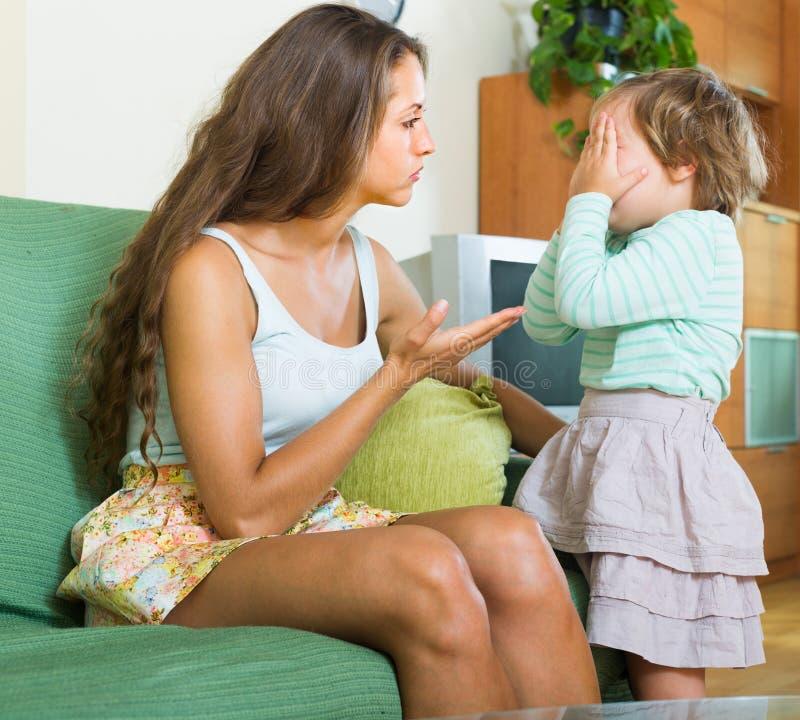 Kvinna som hemma grälar på barnet arkivfoto