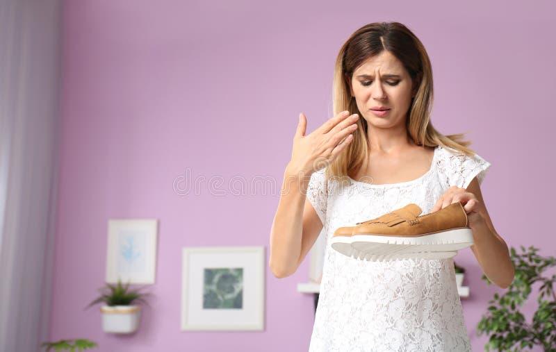 Kvinna som hemma känner den dåliga lukten från skor royaltyfri fotografi