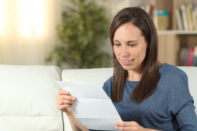 Kvinna som hemma läser ett brev på en soffa royaltyfri fotografi