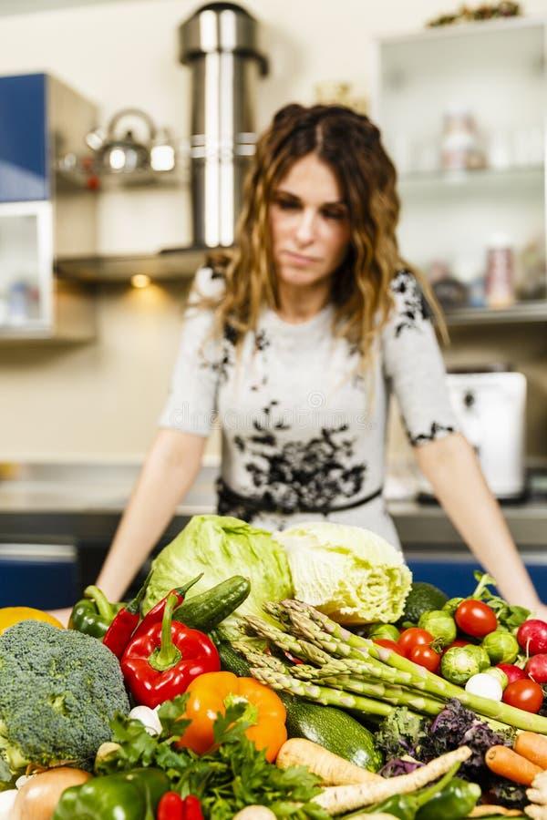 Kvinna som hemma lagar mat och att ha en stor hög av grönsaker på boen royaltyfri foto