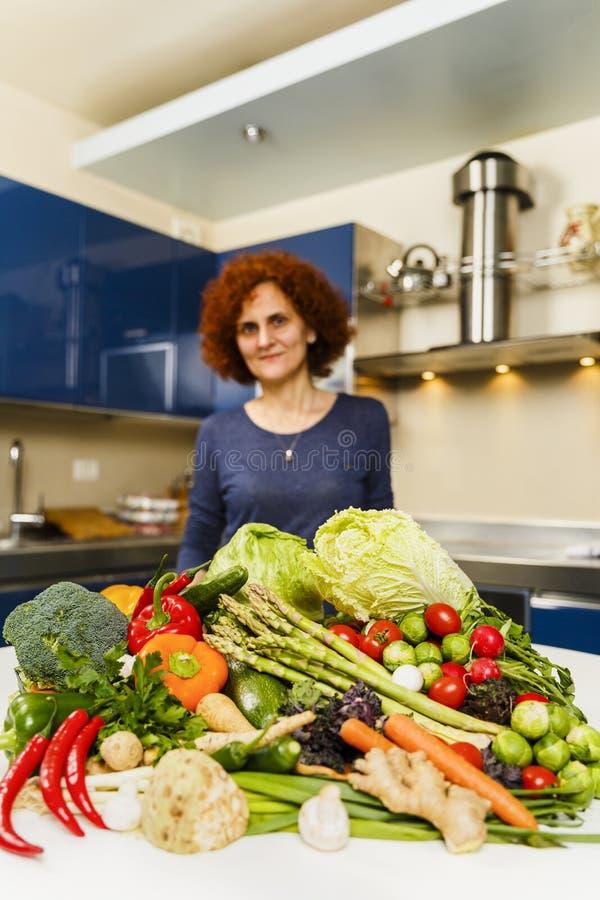 Kvinna som hemma lagar mat och att ha en stor hög av grönsaker på boen royaltyfria foton