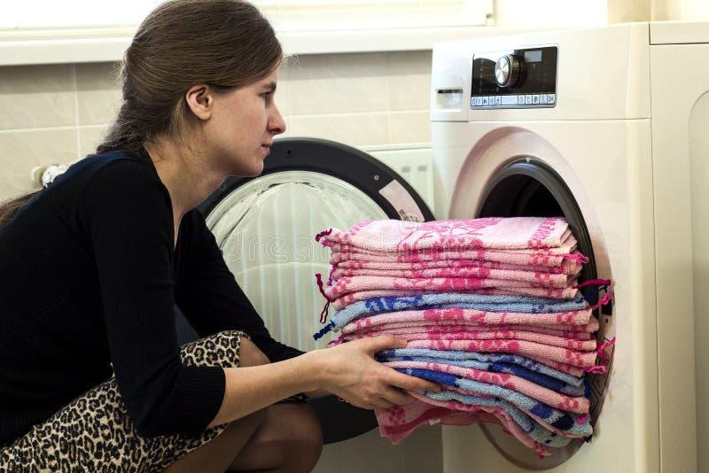 Kvinna som hemma sätter tvätterit in i tvagningmaskinen royaltyfria foton