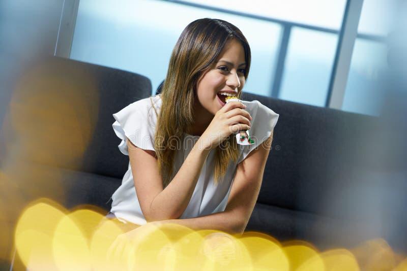 Kvinna som hemma sitter äta den magra sädes- stången royaltyfria foton
