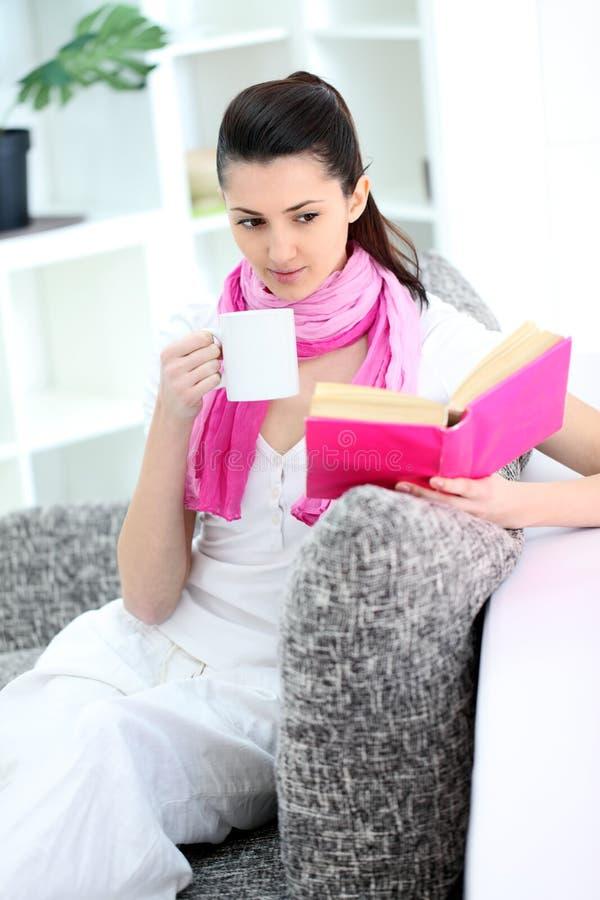 Kvinna som hemma sitter på sofaen fotografering för bildbyråer