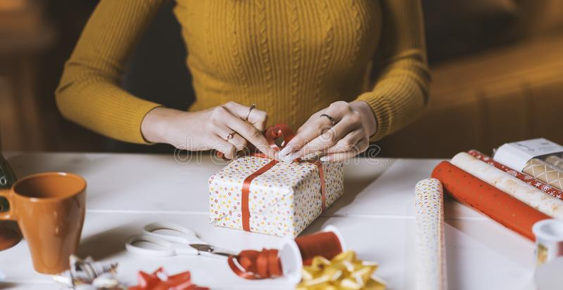 Kvinna som hemma sl?r in julg?vor royaltyfri foto