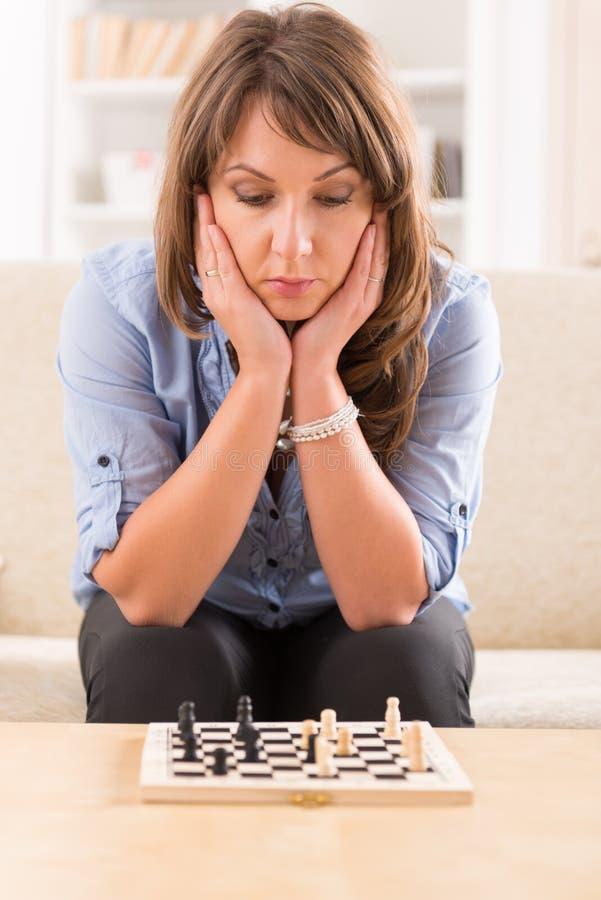 Kvinna som hemma spelar schack arkivfoton