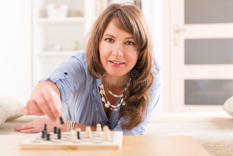 Kvinna som hemma spelar schack royaltyfri foto