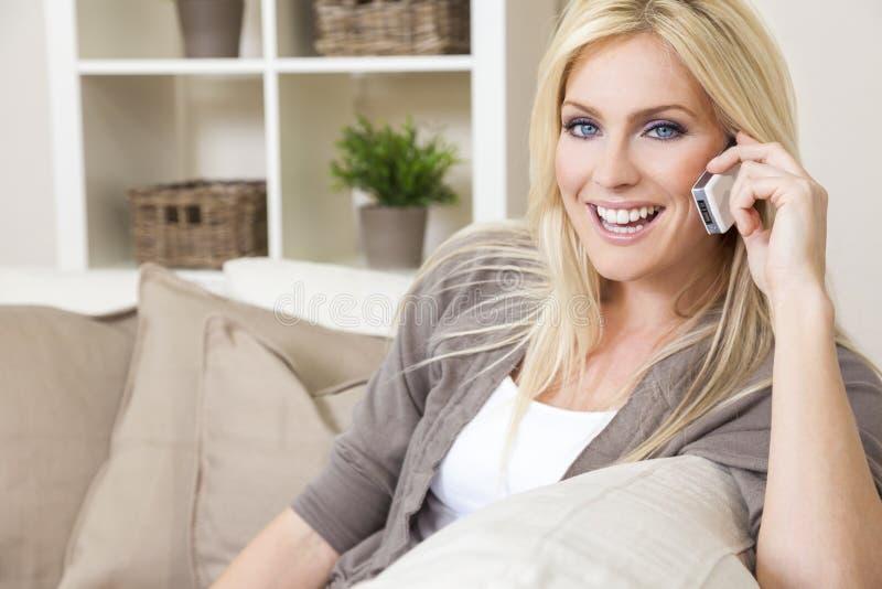Kvinna som hemma talar på mobiltelefonen royaltyfri bild