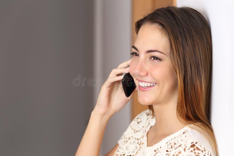 Kvinna som hemma talar på mobiltelefonen eller kontor arkivbilder