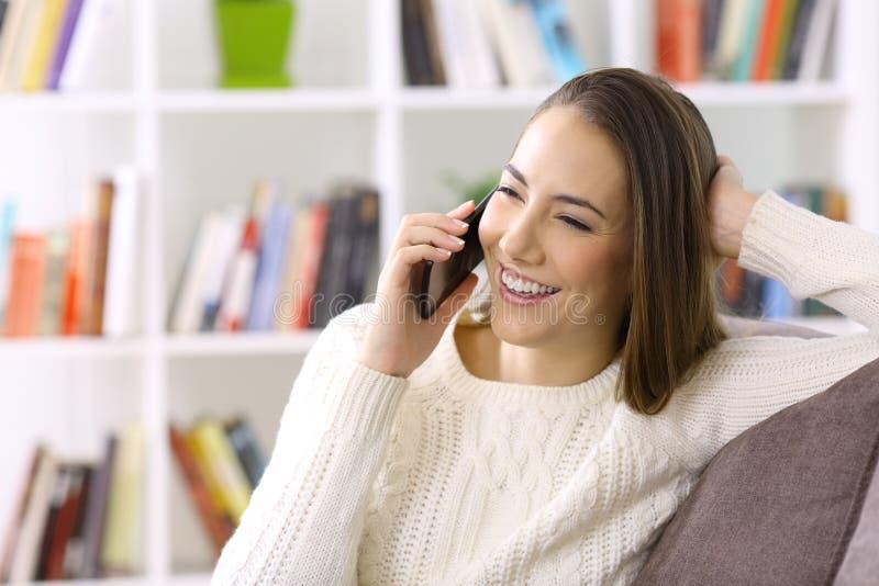 Kvinna som hemma talar på telefonen i vinter royaltyfri foto