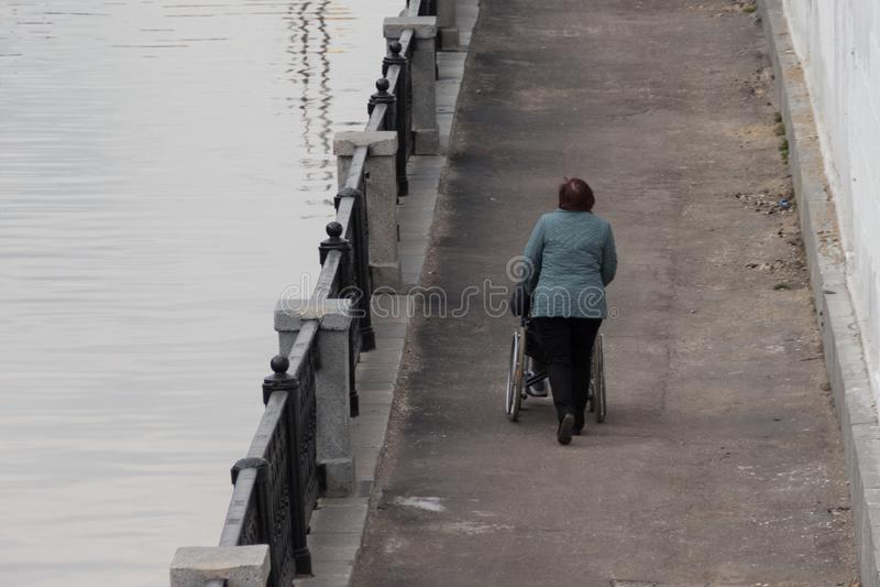 Kvinna som hjälper att rulla en rullstol med en person längs promenaden royaltyfri foto