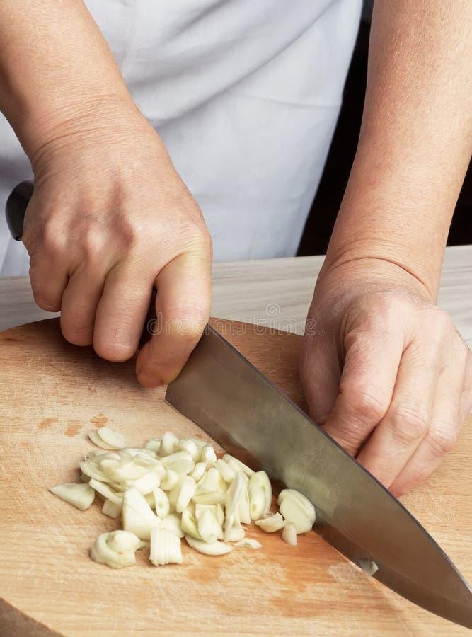 Kvinna som hugger av vitlöken med kniven arkivbild