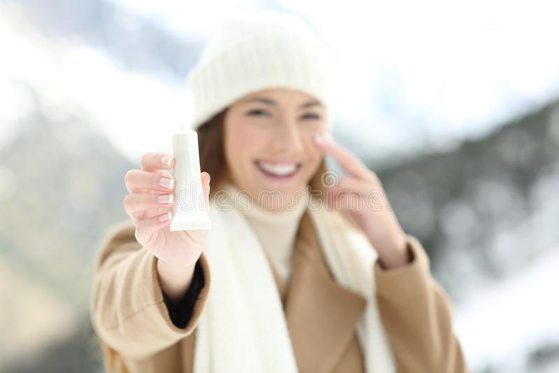 Kvinna som hydratiserar ansikts- hud och visar produkten royaltyfri foto
