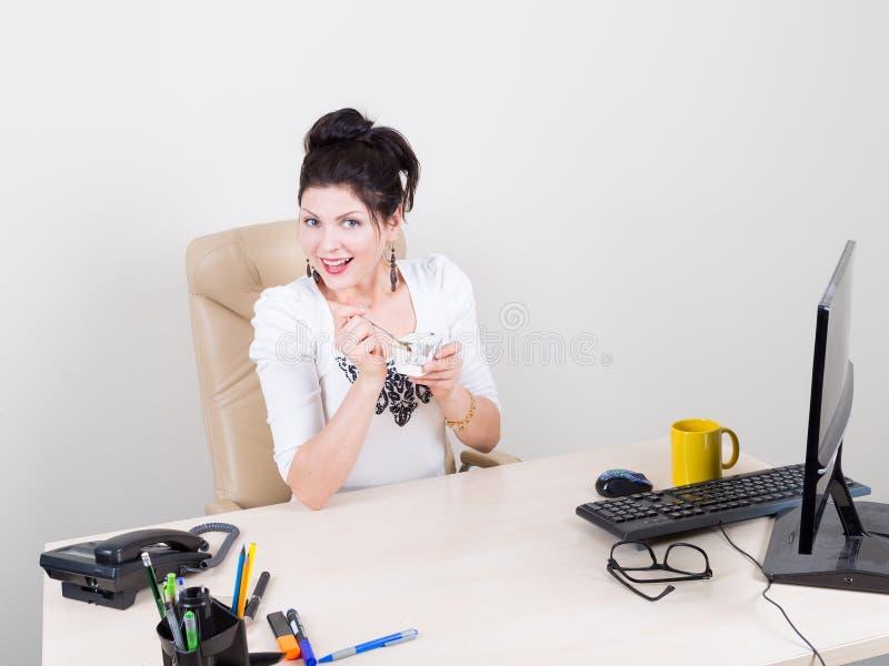 Kvinna som i regeringsställning äter yoghurt arkivbilder
