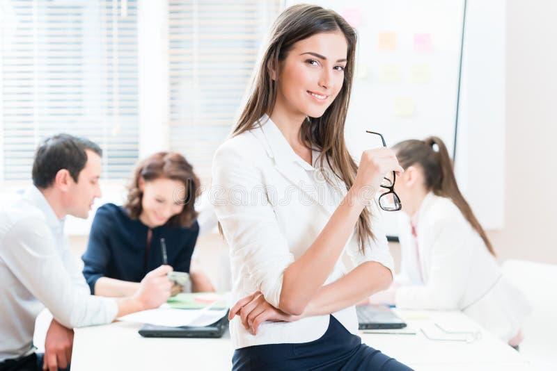 Kvinna som i regeringsställning arbetar, och grupp som har affärsmöte arkivfoton