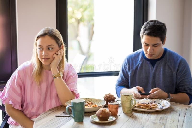 Kvinna som ignorerar pojkvännen under datum arkivfoto