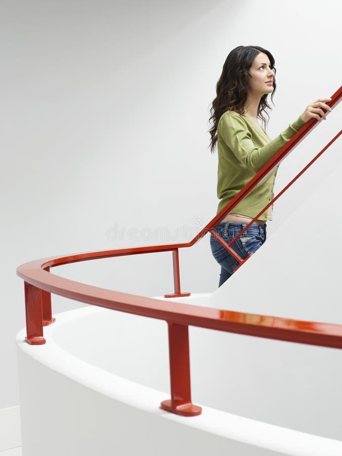 Kvinna som inomhus går upp trappa royaltyfria foton