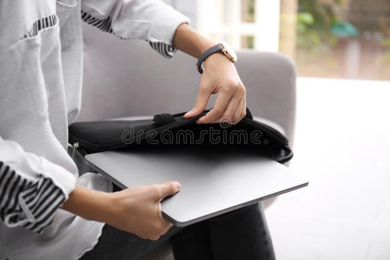 Kvinna som inomhus sätter bärbara datorn in i fall arkivbild