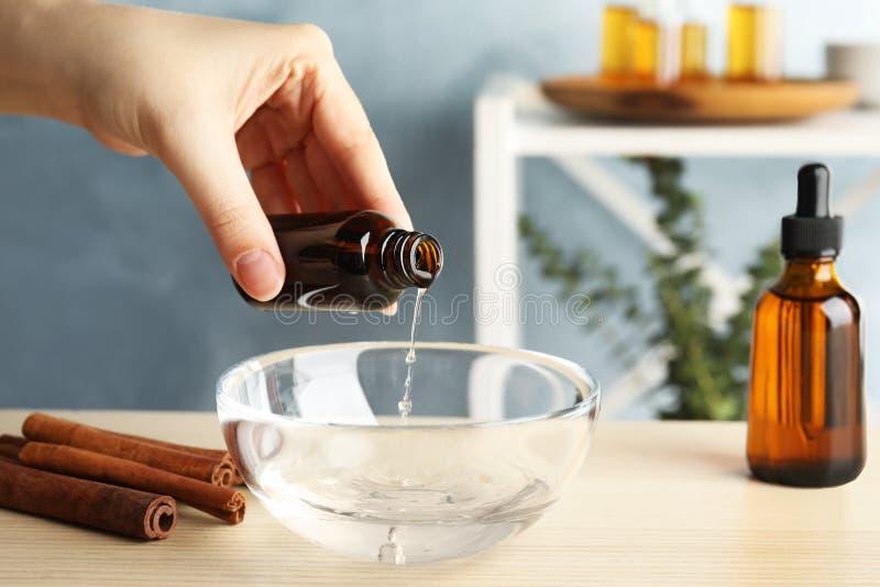 Kvinna som inomhus tillfogar kanelbrun nödvändig olja från flaskan in i bunken av vatten på tabellen arkivfoto