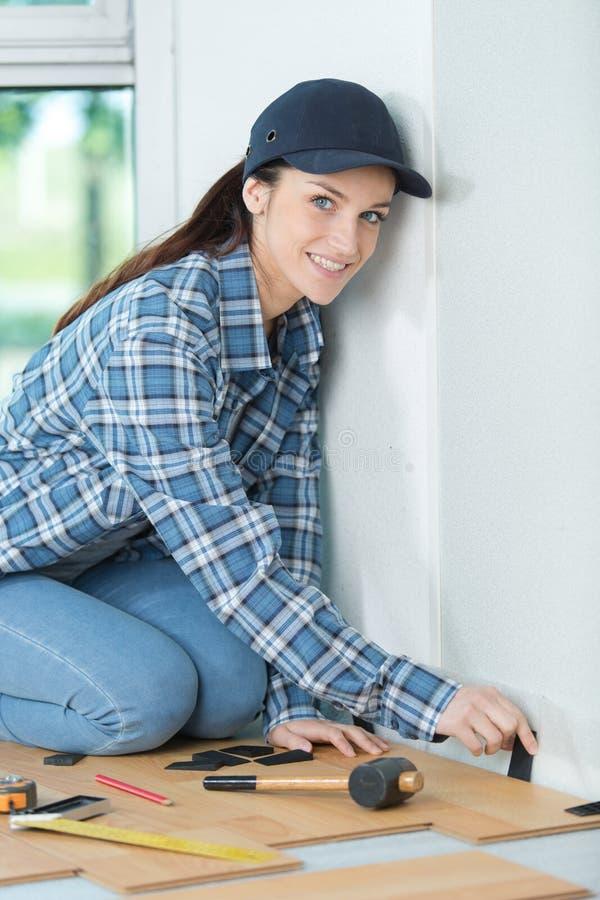 Kvinna som installerar den pläterade durken arkivbilder