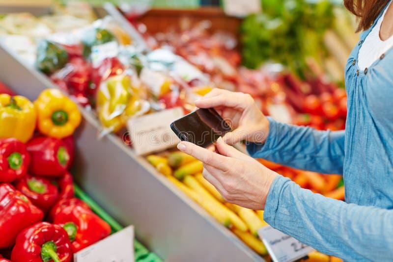 Kvinna som jämför grönsaker med smartphonen royaltyfria bilder