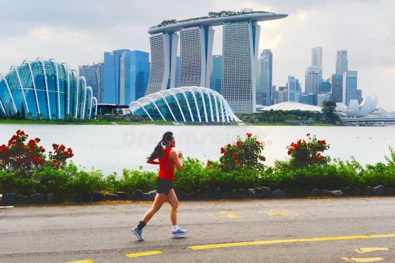 Kvinna som joggar i den Singapore fjärden arkivfoto