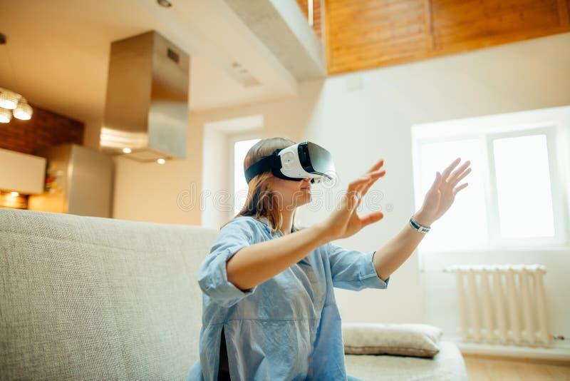 Kvinna som justerar hennes VR-hörlurar med mikrofon och ler, medan sitta på mattan hemma arkivbild