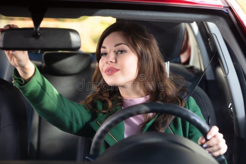 Kvinna som justerar spegeln f?r bakre sikt av en bil royaltyfri fotografi