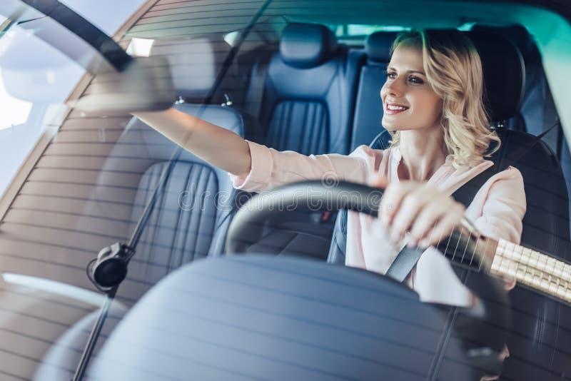 Kvinna som justerar spegeln för bakre sikt i bil royaltyfria bilder