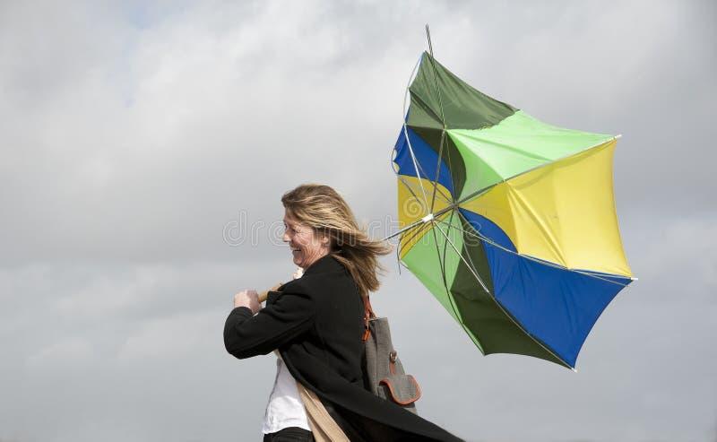 Kvinna som kämpar för att rymma hennes paraply på en blåsig dag arkivbild