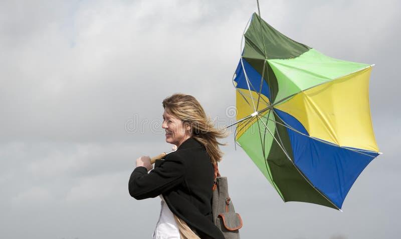 Kvinna som kämpar för att rymma hennes paraply på en blåsig dag royaltyfria foton
