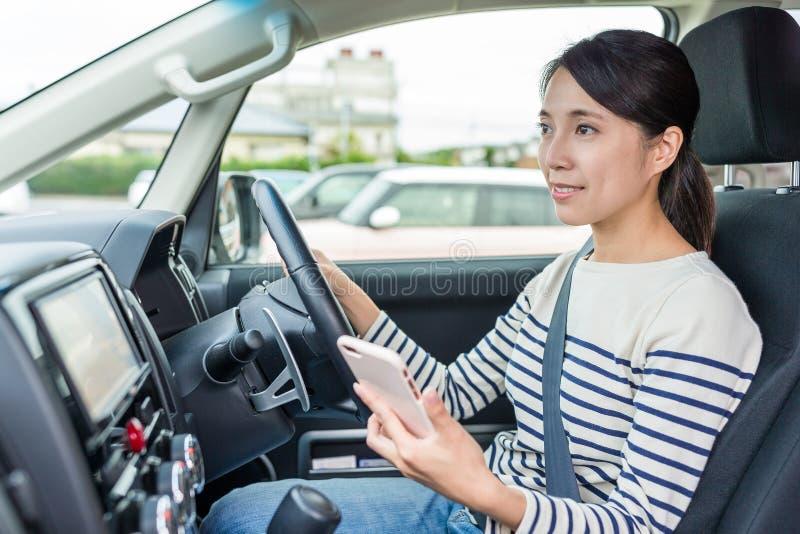 Kvinna som kör bilen och använder mobiltelefonen fotografering för bildbyråer