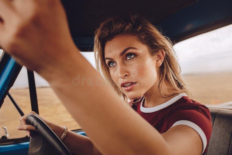 Kvinna som kör bilen och ställer in spegeln för bakre sikt arkivbilder