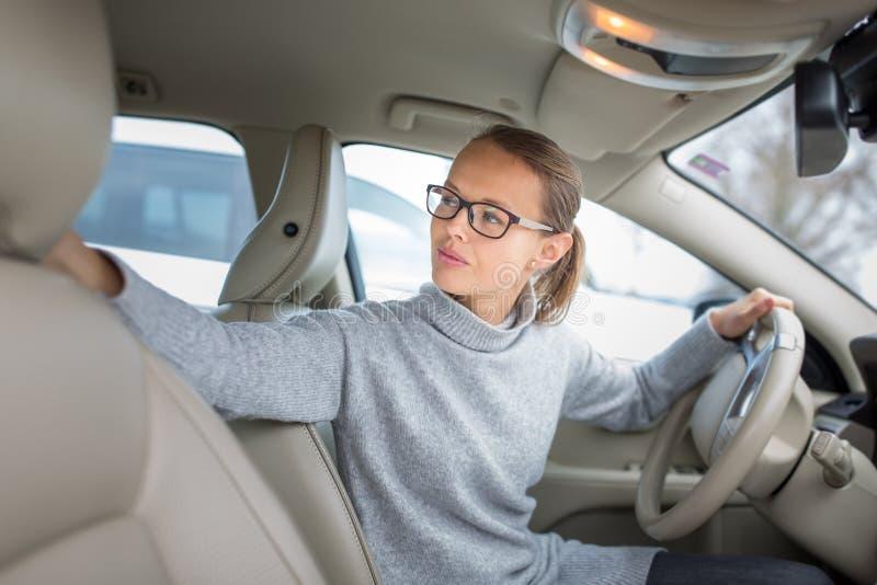 Kvinna som kör en bil- parkering som går i omvänt royaltyfri bild
