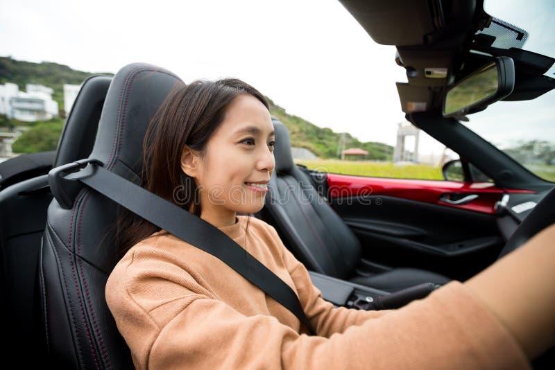 Kvinna som kör en konvertibel sportbil fotografering för bildbyråer