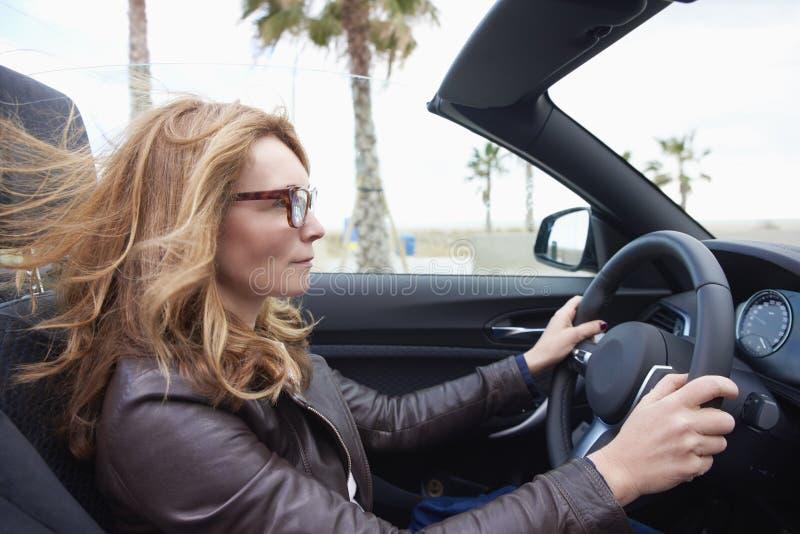 Kvinna som kör hennes cabrioletsportbil royaltyfri bild