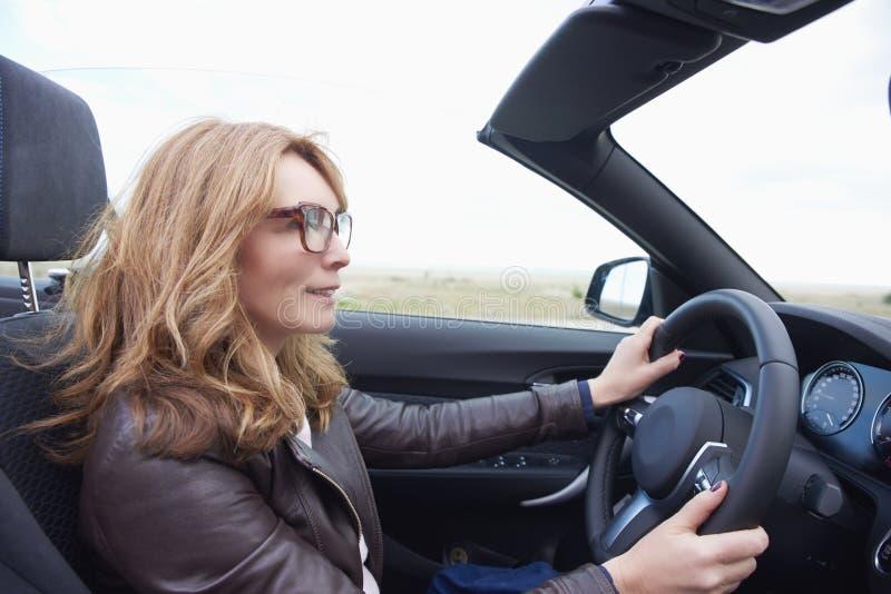 Kvinna som kör hennes cabrioletsportbil arkivfoto