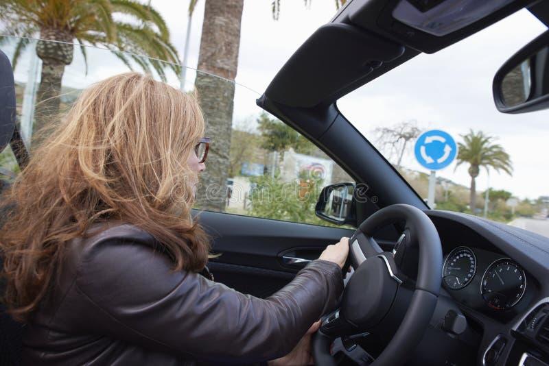 Kvinna som kör hennes cabrioletsportbil arkivbilder