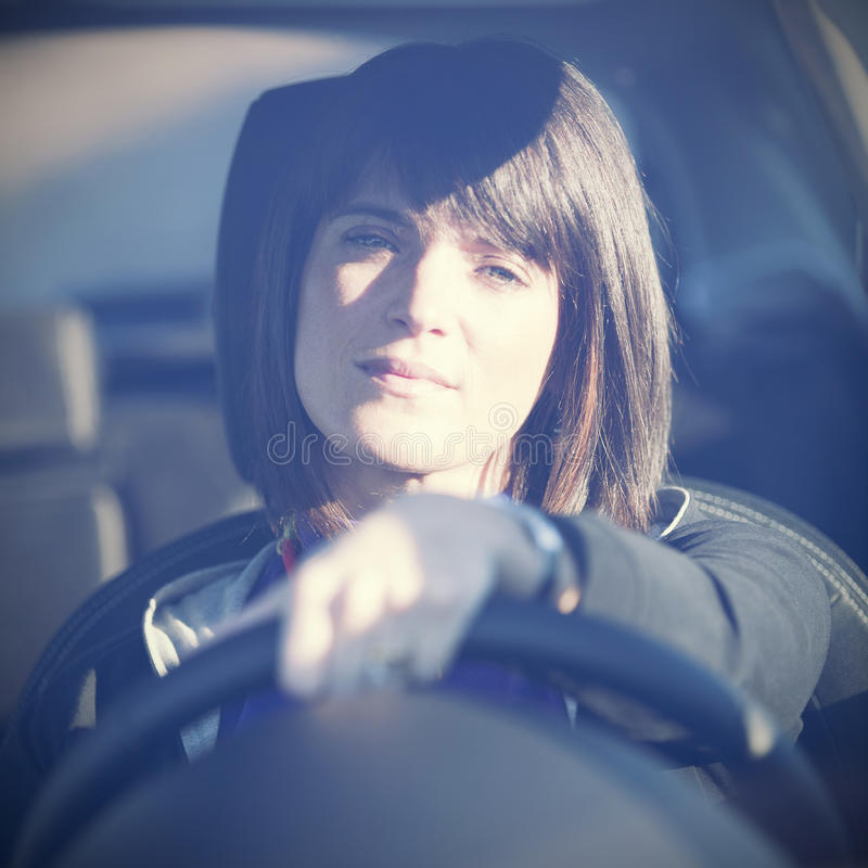 Kvinna som kör hennes nya bil fotografering för bildbyråer