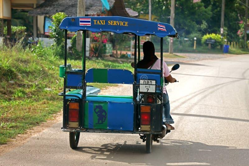Kvinna som kör taxien för anslutningstrehjulingmotorcykel på gatan i Koh royaltyfria foton