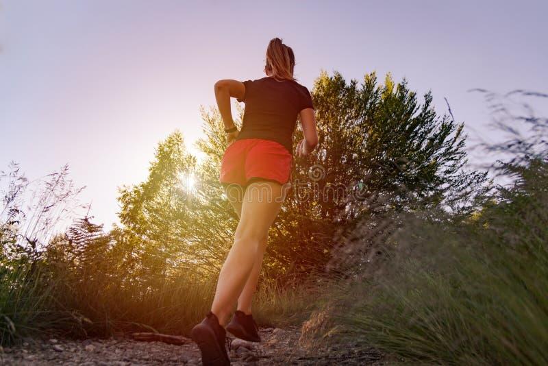 Kvinna som k?r i bergen p? solnedg?ngen royaltyfri foto